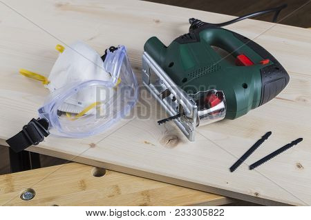 Jig Saw With Goggles Mask And Blades On A Workbench