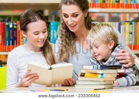 Class of children students with their teacher in the school library reading and learning