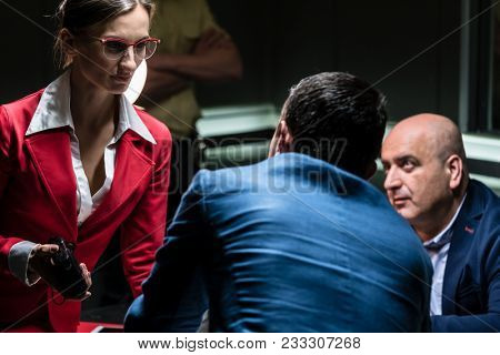 Dedicated female prosecutor holding an audio recorder while listening to the confession of a middle-aged suspect in the office of a police station