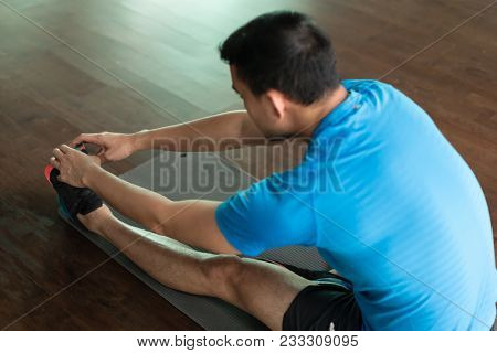 Low-angle full length view of a man sitting down on exercise mat while touching his toes during stretching routine at the gym