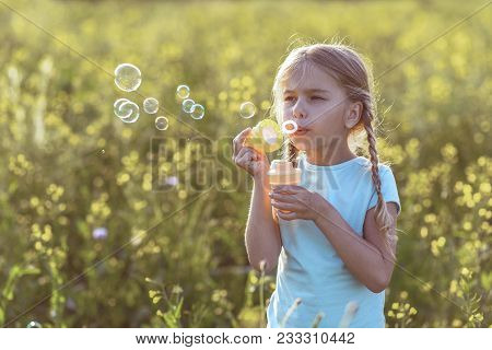 Portrait Of Calm Female Child Inflating Soap Bubbles In The Nature