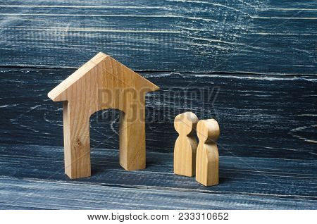 Two People Stand Near The House And Evaluate Its Qualities Before Buying. The Concept Of Buying And