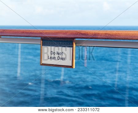 Warning Sign Do Not Lean Over On The Teak Railing Of Cruise Ship Above The Ocean