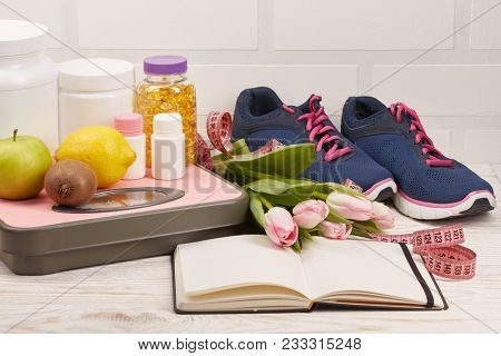 Female fitness still life with copy space.  Sports  nutrition (supplements), sport accessories and dumbbells isolated on a white background. Healthy lifestyle concept.
