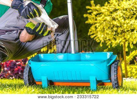 Lawn Spring Fertilization. Caucasian Gardener Resupply His Fertilization Tool. Fertilize Turf In Lat