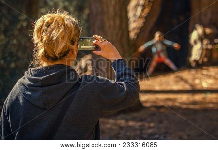 Taking Family Photos And Videos Using Smartphone. Caucasian Woman In Her 30s Talking Photo Of Her Da