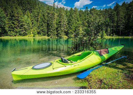 Scenic Kayak Trip. Green Single Kayak On The Shore Of Scenic Alpine Lake.