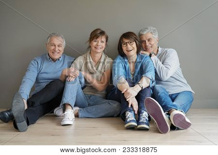 Group of happy senior people sitting on floor against wall, isolated