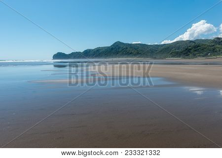 The Sky And Clouds Reflected On The Wet Sand At Piha Beach New Zealand