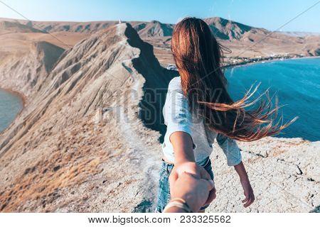 Girl walking on the mountain top over blue sea view. Follow me - POV.