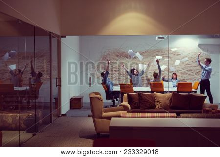 Group of young business people throwing documents and looking happy while celebrating success at their working places in night office