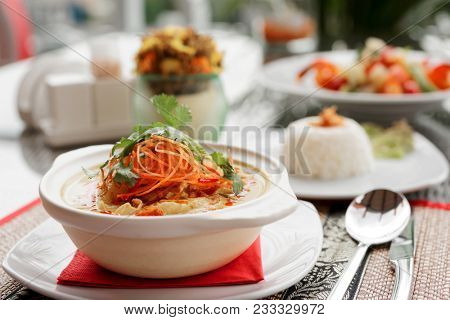 Bowl of spicy curry dish with coconut milk on restaurant table outdoors, toned