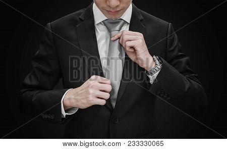 A Man In Black Suit Tying Gray Necktie On Black Background