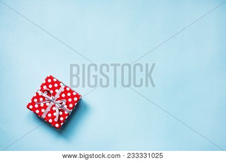 Top View Of A Red Dotted Gift Box Tied With Golden Bow Over Blue Background. Copy Space.