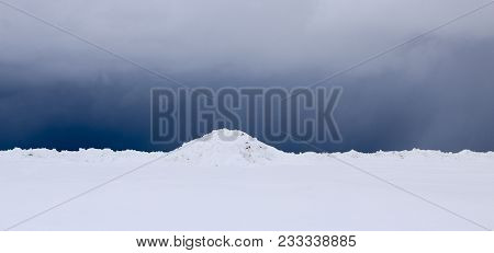 Snow Field. The Plain Is Covered With White Snow Under A Blue Sky With Thick White Clouds. Before A