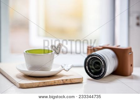 Cup Of Green Tea  And Classic Camera On White Table
