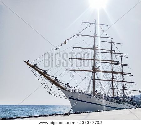 White Three-mast Ship Or Frigate Anchored At Blue Sea Background