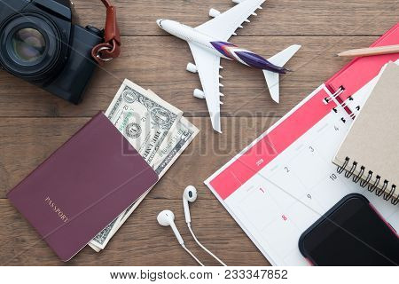 Passport, Camra, Mobile Phone And Calendar With Airplane Model On Wooden Table, Travel Concept, Flat