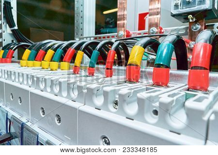 A range of electrical wires or cables are connected to the power circuit breakers. Black wires are marked in different colors. In the background, the design of the electrical Cabinet with busbars. poster