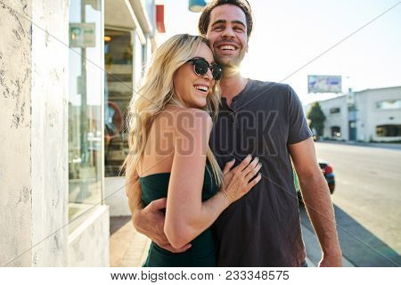 attractive flirty romantic couple having fun walking down sidewalk in los angeles together