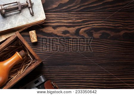 Retro table with vintage items. Camera, books, wine bottle. Top view with space for your text