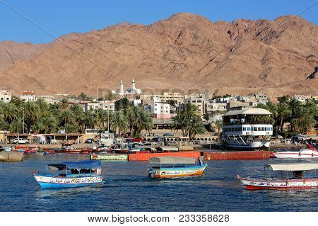 Aqaba, Jordan - March 17, 2016: Glass Boats On The Red Sea Coast With The Town Of Aqaba And Mountain