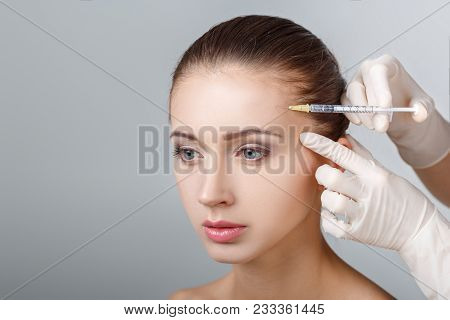 Portrait Of Young Beautiful Woman Getting Cosmetic Lifting Injection In Forehead. Plastic Surgery. C
