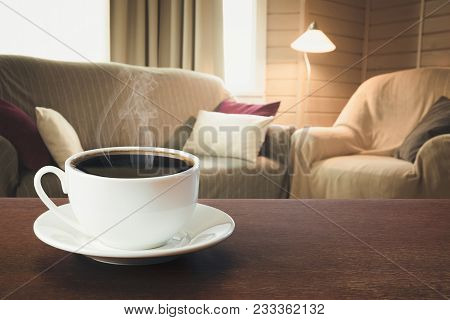 Hot Cup Of Black Coffee On Tabletop In Modern Living Room In Rustic Style With Chair, Soft Divan.