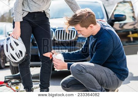 Young male driver using a sterile adhesive bandage from his first aid kit to help an injured female bicyclist on the street poster