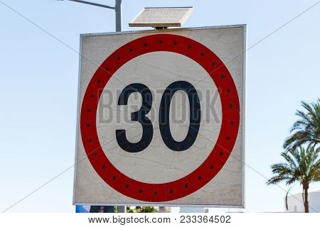 Speed Limit Sign To 30 With Solar Panel On The Road.