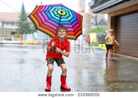 Kid Boy Wearing Red Rain Boots And Walking With Colorful Umbrella On City Street. Child With Glasses