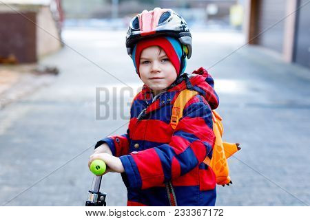Cute Little Preschool Kid Boy Riding On Scooter Riding To School. Children Activities Outdoor In Win