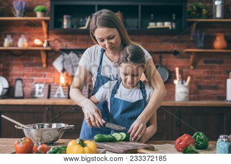 Mother And Daughter Cooking Salad On The Kitchen. Happy Family Concept