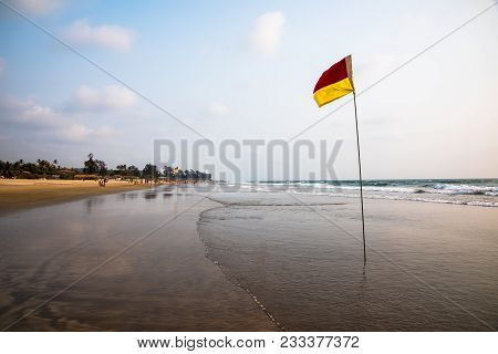 Red And Yellow Lifeguard Flag On Beach Marking Safe Zone For Swimming And Surfing