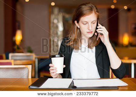 Portrait Of Busy Young Caucasian Businesswoman Drinking Coffee And Talking To Client On Mobile Phone