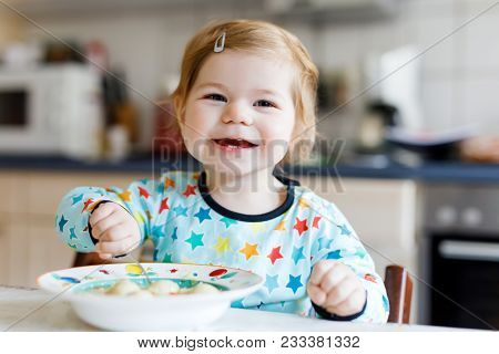 Adorable Baby Girl Eating From Spoon Vegetable Noodle Soup. Food, Child, Feeding And Development Con