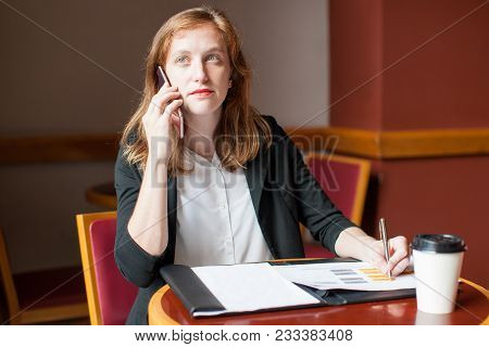 Portrait Of Young Caucasian Businesswoman Talking To Client On Mobile Phone In Cafe. Self-employed P