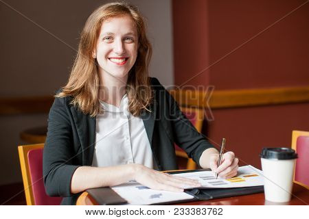 Portrait Of Young Caucasian Businesswoman Working With Document And Smiling In Office. Self-employed