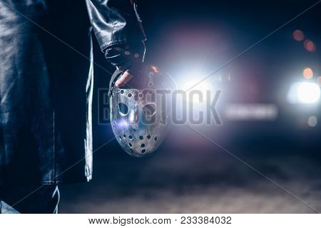 Serial maniac hand with bloody hockey mask closeup