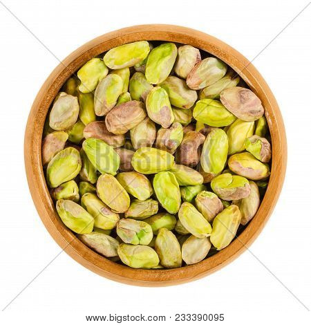 Shelled, Roasted Pistachios In Wooden Bowl. Green Seeds And Ripe Fruits Of Pistacia Vera, Used As Sn