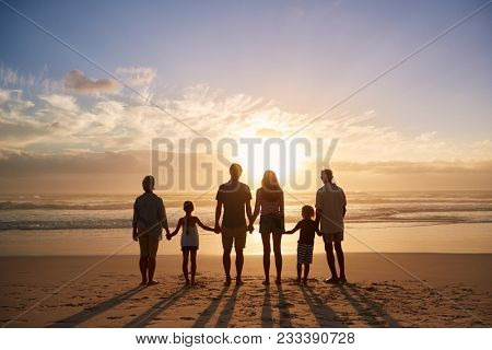 Rear View Of Multi Generation Family Silhouetted On Beach