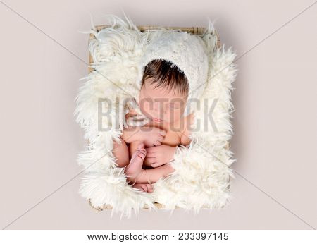 Newborn baby asleep on back with legs curled up