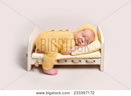 Baby dressed in knitted yellow costume sleeping on crib