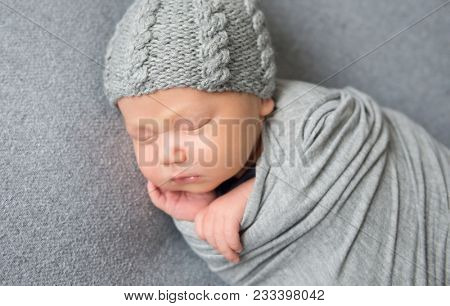 Newborn baby sleeping curled up in grey blanket