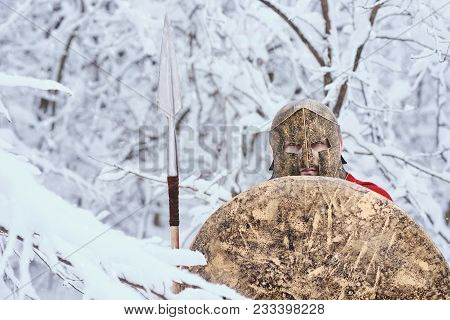 Spartan Man Took Shelter Under Snowy Branches In Winter Forest. He Kaaps Big Round Shield In One Han