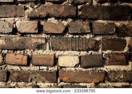 Brick wall, old dark brick. Pattern of the structure of a brick wall with masonry. Old wall European home