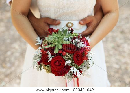 The Bridegroom Embraces The Bride's Waist, A Wedding Bouquet In Her Hands, In Focus A Bouquet