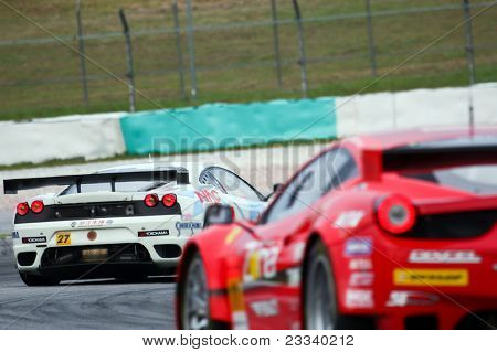 SEPANG, MALAYSIA - JUNE 19: LMP Motorsport's white Ferrari takes turn 4 ahead of the Jimgainer's red Ferrari during the Japan SUPER GT Round 3 race on June 19, 2011 in Sepang International Circuit, Sepang, Malaysia.