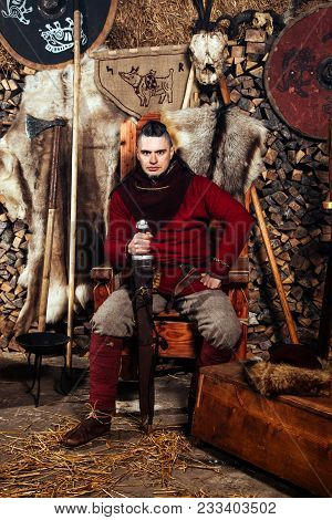 Serious militant Viking stands with a weapon in his hands. Portrait of a warrior in ancient clothes with a gun in his hand against the backdrop of skins and flags of the Vikings. poster