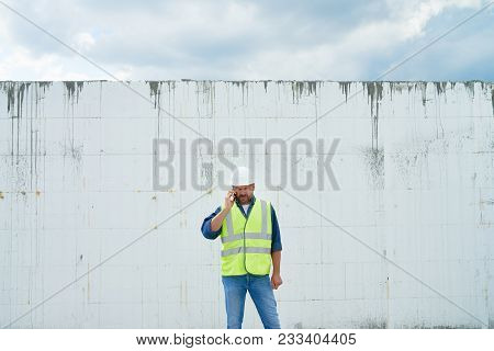 Portrait Of Mature Construction Worker Speaking By Phone Standing By Wall Of Unfinished Building, We